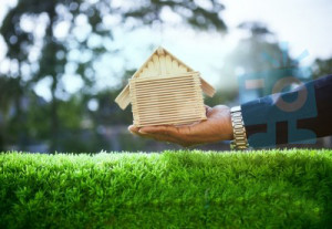 hand-of-business-man-and-wood-house-model-on-beautiful-green-gra-100255663 copy